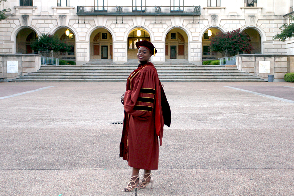 Adèle Douglin, pictured wearing academic regalia and standing in front of UT-Austin's Main Building, completed her PhD in Foreign Language Education in May 2017.