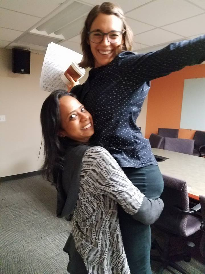 Caitlin McClune's friend Shalmali lifts her up at the end of her successful dissertation defense